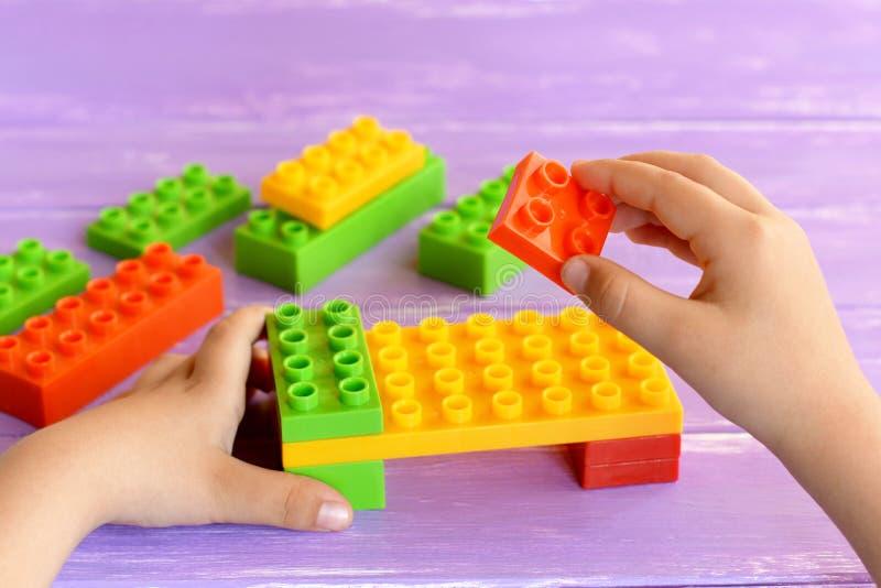 Małe dziecko trzyma projektanta bloki w jego rękach i robi łóżko zabawce Barwiony plastikowy konstruktor na lilym tle zdjęcie stock