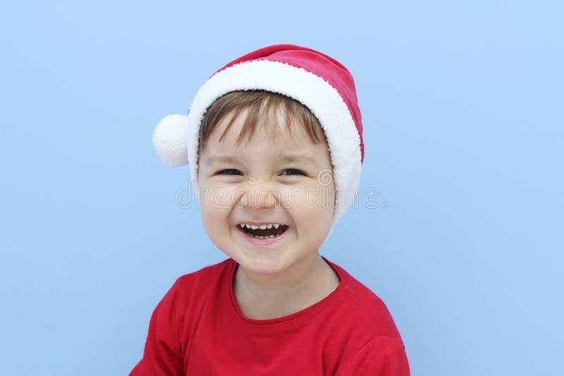 Małe dziecko ubierający jako Santa Claus śmiać się obraz stock