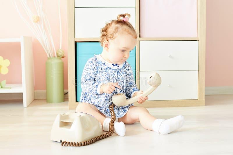 Małe dziecko w studiu bawić się z telefonem zdjęcia stock