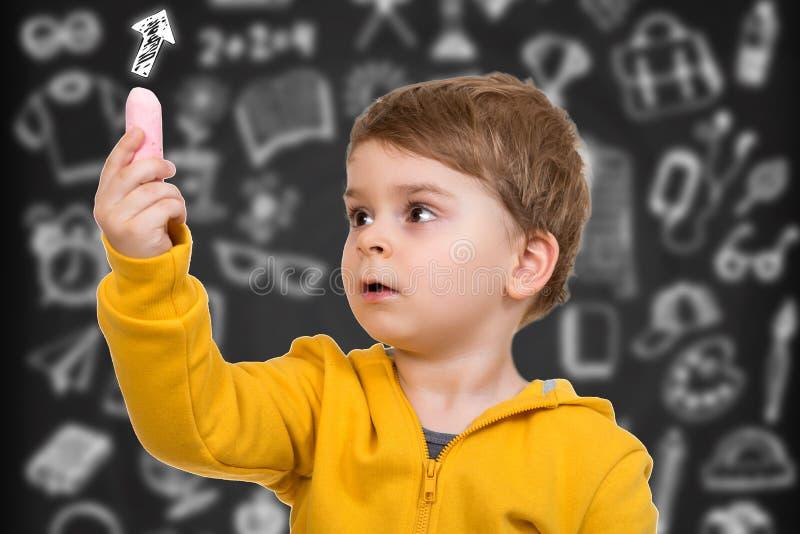 Małe dziecko wokoło rysować coś z kredą zdjęcie stock