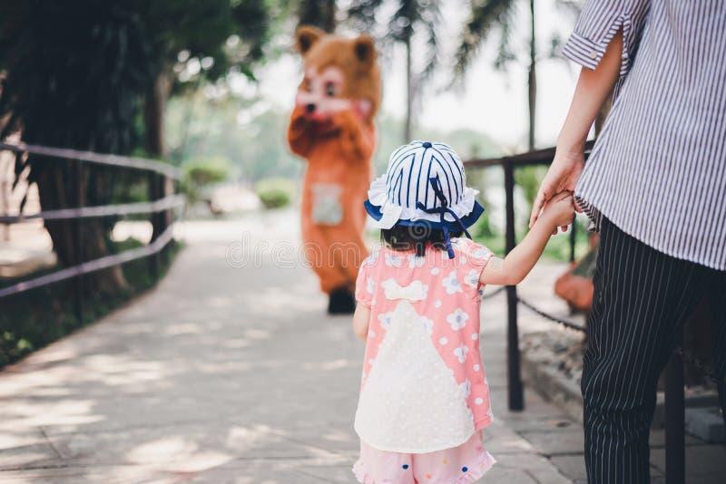 Małe dziecko z macierzystą mienie ręką chce bawić się z niedźwiedziem zdjęcia royalty free