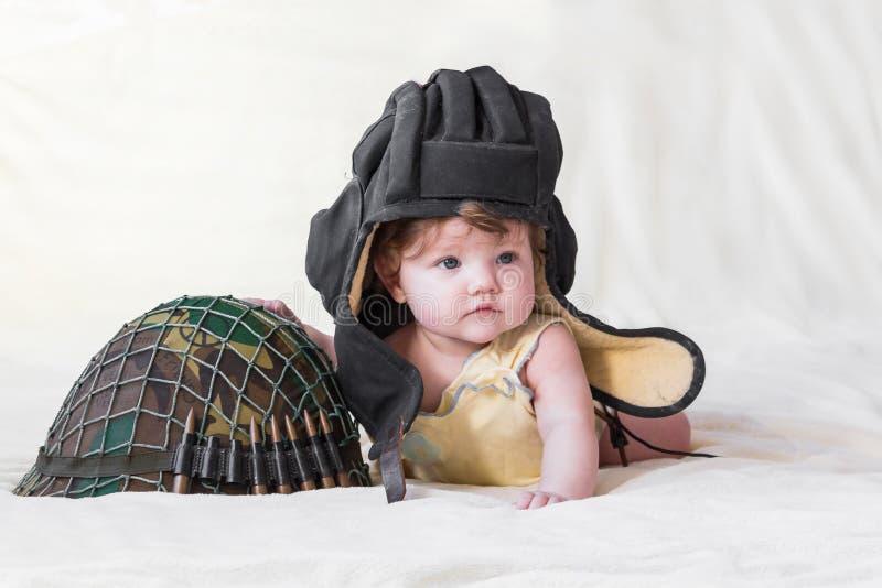 Małe dziecko z militarnym hełmem fotografia stock