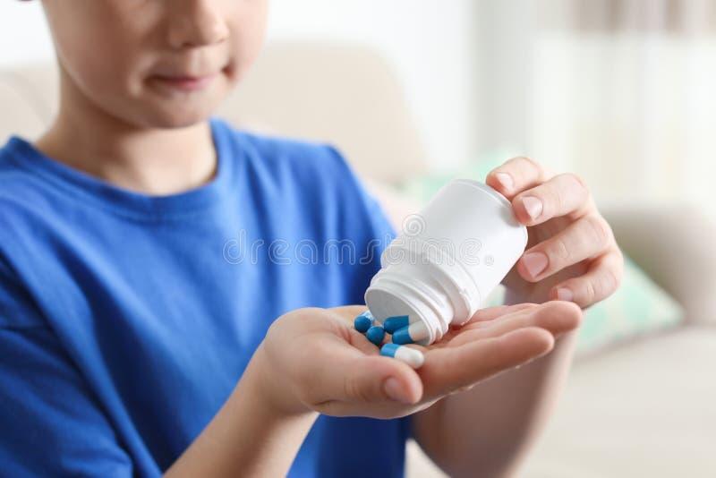 Małe dziecko z pigułkami w domu, zbliżenie Niebezpieczeństwo medicament zdjęcie royalty free