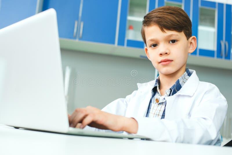 Małe dziecko z uczenie klasą w szkolnym laboranckim używa laptopie zdjęcia royalty free