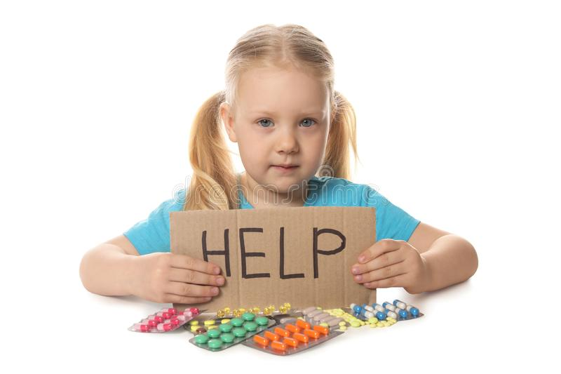 Małe dziecko z wiele różnymi pigułkami i słowo Pomagamy piszemy na kartonie Niebezpieczeństwo medicament zdjęcie royalty free