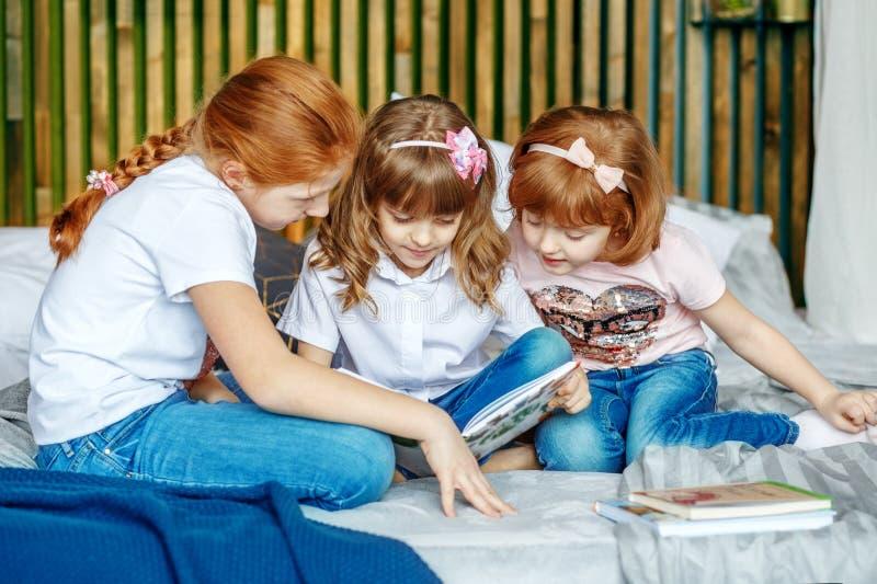 Małe dziewczynki considering książkę Pojęcie styl życia, c zdjęcie stock