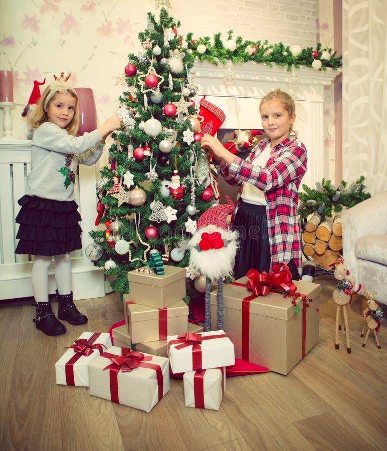 Małe dziewczynki dekoruje choinki i przygotowywa prezenty fotografia stock