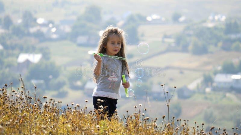 Małe dziewczynki dmucha mydlanych bąble zdjęcia royalty free