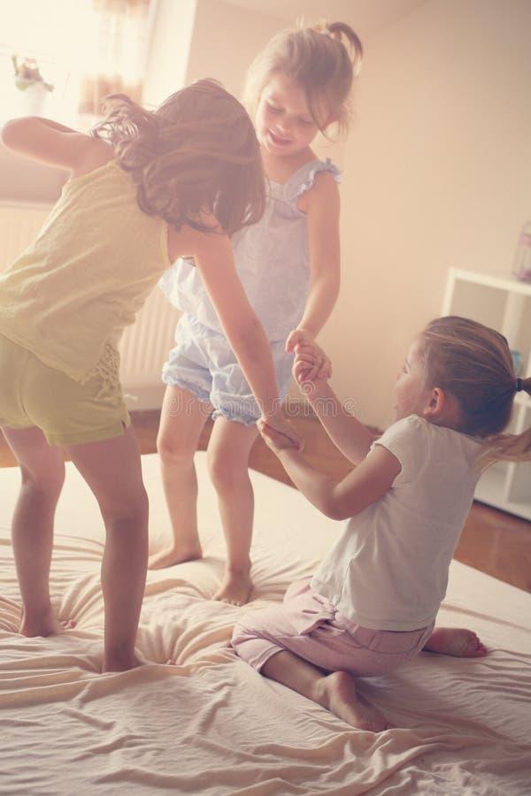 Małe dziewczynki ma zabawę w łóżku wpólnie zdjęcie stock
