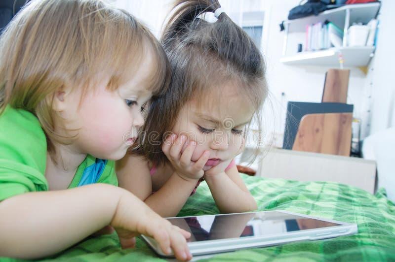 Małe dziewczynki patrzeje na ochraniacza lying on the beach na łóżku w domu obrazy stock