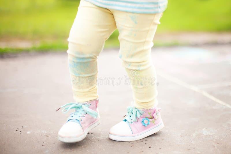 Małe dziewczynki plamiący spodnia po rysunkowego wirh koloru piszą kredą obrazy royalty free