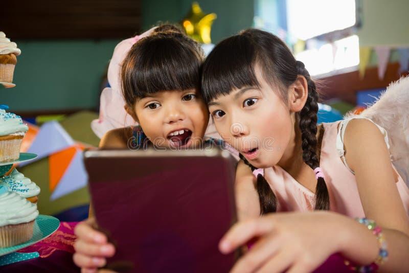 Małe dziewczynki używa pastylkę przy przyjęciem zdjęcia stock