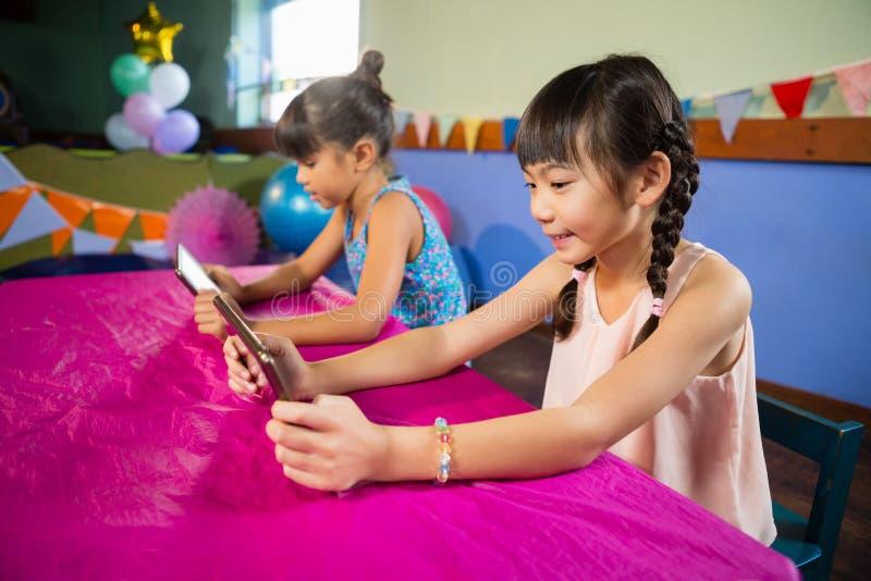 Małe dziewczynki używa pastylkę przy przyjęciem obrazy stock