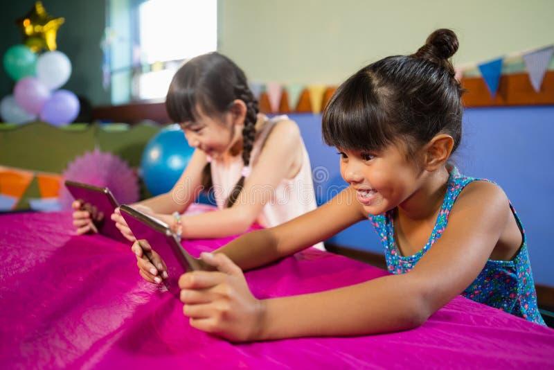 Małe dziewczynki używa pastylkę przy przyjęciem fotografia royalty free
