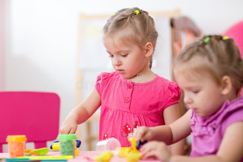 Małe dziewczynki uczy się pracować kolorowego sztuki ciasto obrazy royalty free
