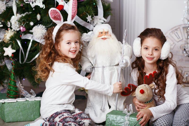 Małe dziewczynki w wygodnego domu odzieżowym obsiadaniu na podłoga w bea obrazy royalty free