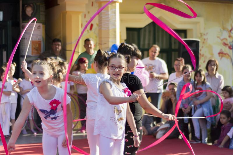Małe dziewczyny tanczy z kolorowym faborkiem na scenie zdjęcia stock