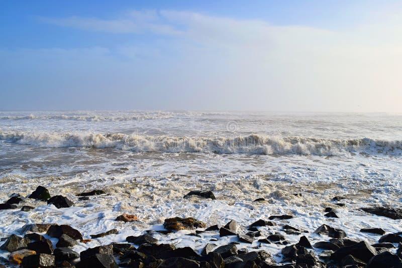 Małe fale na spokojnym oceanie w skalistym wybrzeżu w niedzielę z błękitnym niebem - naturalne tło - Ocean Indyjski w Dwarce, Guj obrazy stock