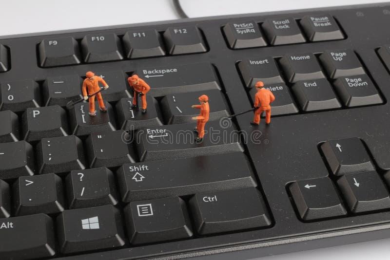 Małe figurki pracownicy naprawia komputerową klawiaturę zdjęcia royalty free