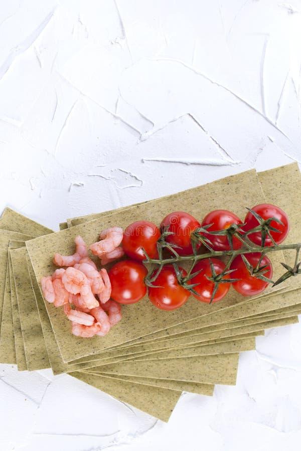 Małe garnele na lasagna prześcieradłach i czereśniowych pomidorach na białym betonowym tle, obrazy stock