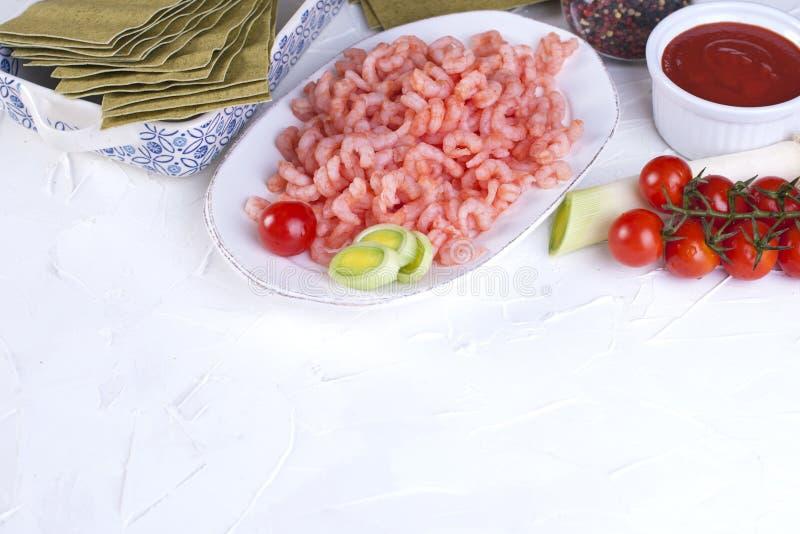 Małe garnele na talerzu, lasagna prześcieradłach i czereśniowych pomidorach na białym betonowym tle, zdjęcie royalty free
