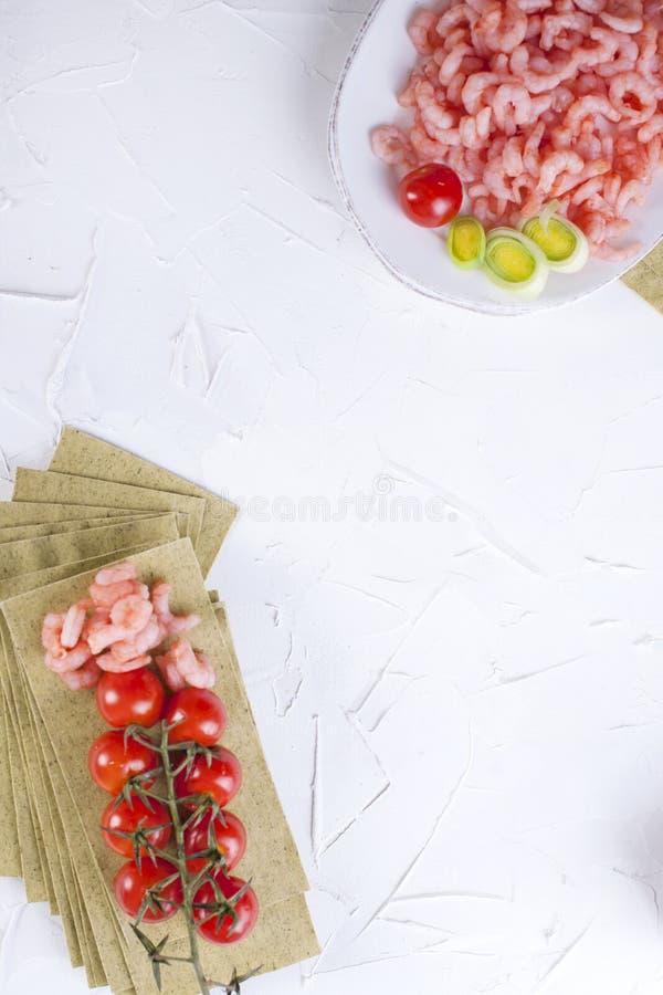 Małe garnele na talerzu, lasagna prześcieradłach i czereśniowych pomidorach na białym betonowym tle, obrazy stock