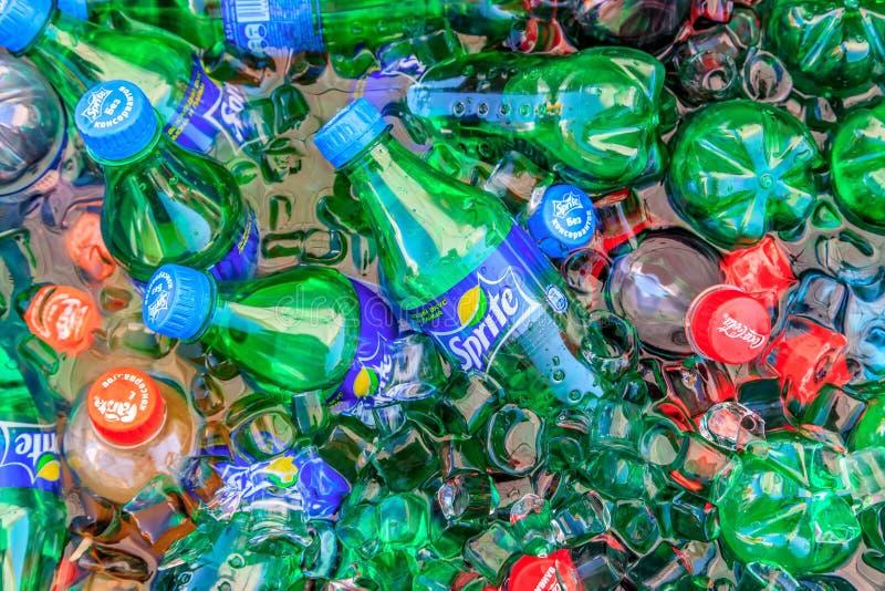 Małe kolorowe plastikowe butelki Sprite, koka-koli i Fanta bezalkoholowi napoje dostaje chłodno w wodzie z lodowymi cegłami, Zako obrazy stock