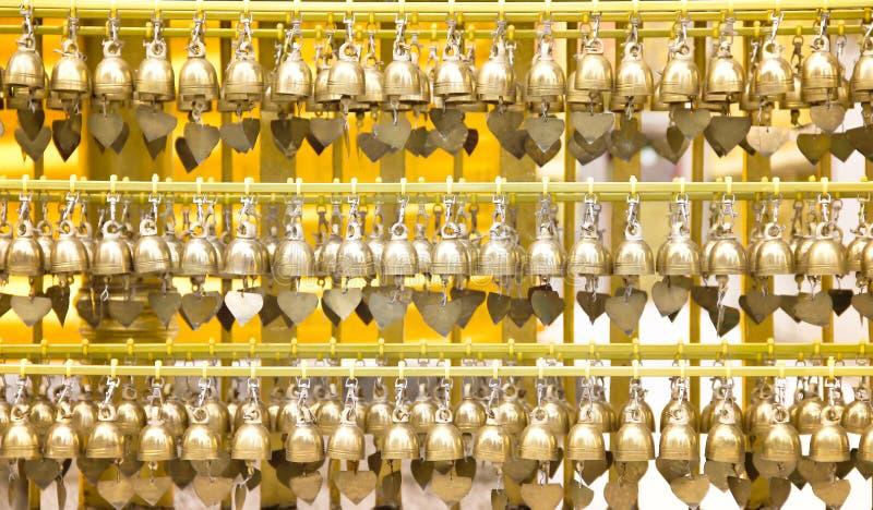 Małe mosiężne dzwony modlące się o wielką grupę wiszącą w stalowej linii w świątyni Phra Hariphunchai w Lamphun, Tajlandia obrazy stock