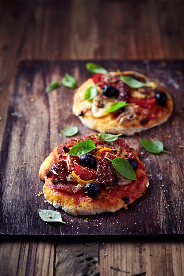 Małe pizze z mozzarellą, salami i wysuszonymi pomidorami, obraz royalty free