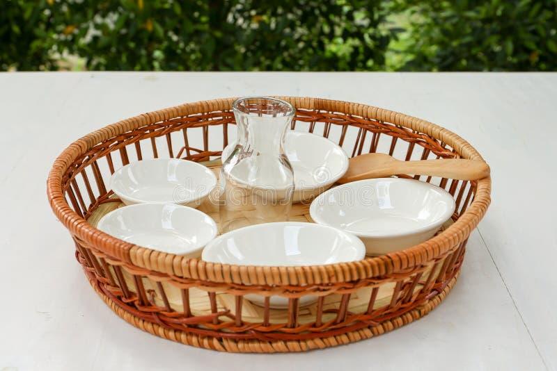 Małe porcelan filiżanki w bambusowym koszu z bokeh tłem zdjęcia royalty free