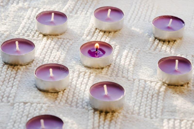 Małe, purpurowe, aromatyczne świeczki na białym tle, obraz stock