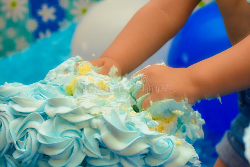 Małe ręki roztrzaskuje tort w urodziny obrazy stock