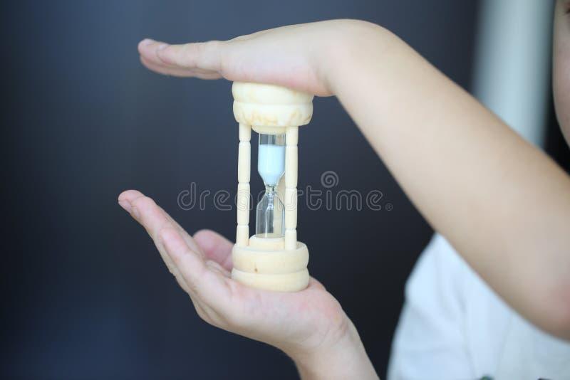 Małe ręki trzymają eleganckiego hourglass z błękitnym piaskiem w one, pojęcie czas wartość zdjęcie royalty free
