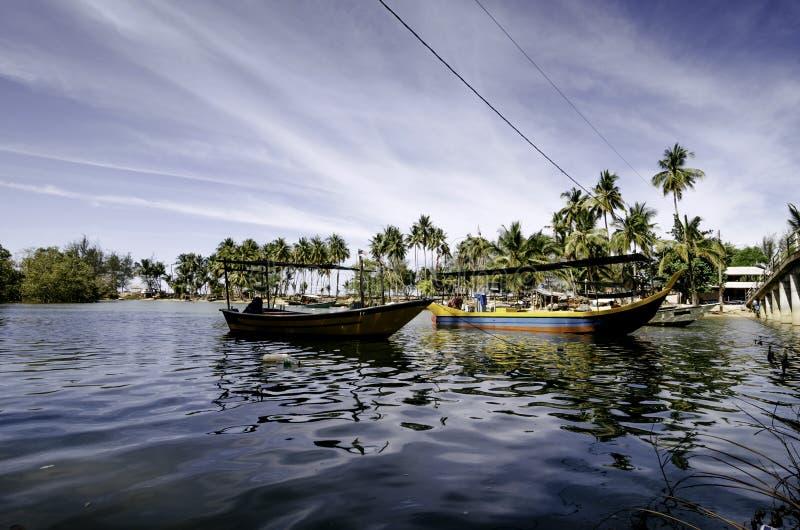 Małe rybaka włókna łodzie zakotwiczali przy brzeg z niebieskiego nieba tłem obraz stock