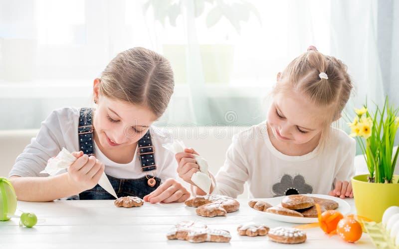 Małe siostry zakrywa Wielkanocnych miodowniki z glazerunkiem obraz royalty free