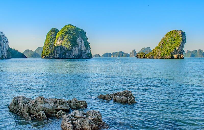 Małe skały nieatutowe przed nadzwyczajnymi kras w Halong zatoce Vietna fotografia stock