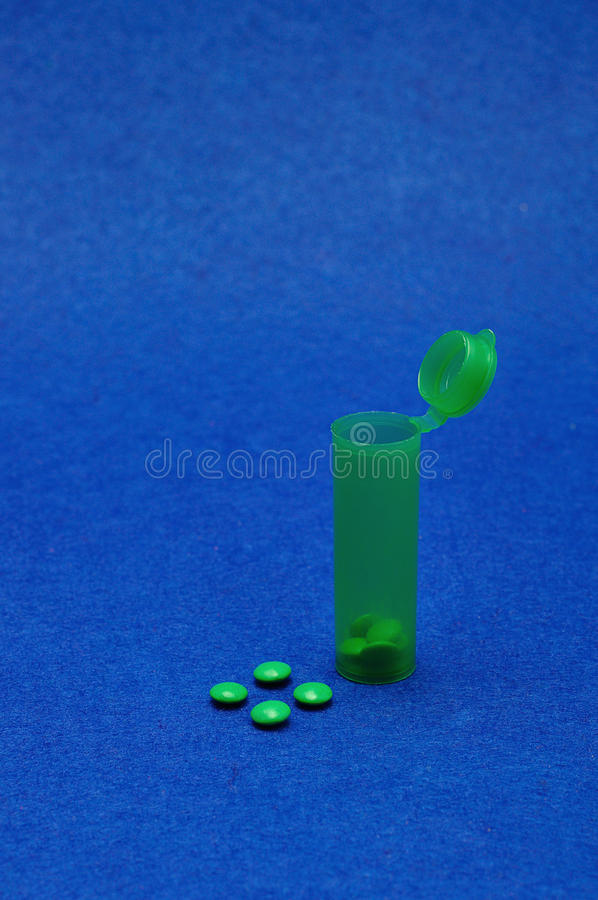 Małe zielone pigułki z zieloną pigułki butelką troszkę obraz royalty free