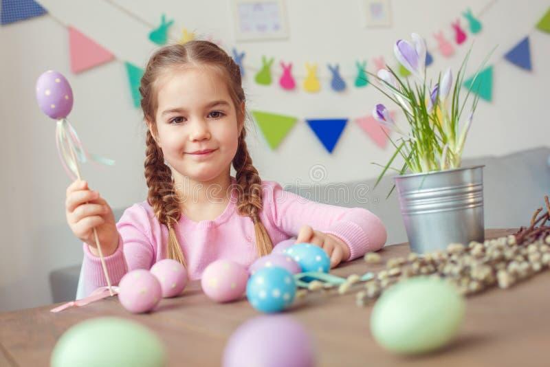 Małego ślicznego dziewczyny Easter świętowania pojęcia siedzącego mienia dekoracyjny jajko na kija ono uśmiecha się w domu zdjęcie royalty free