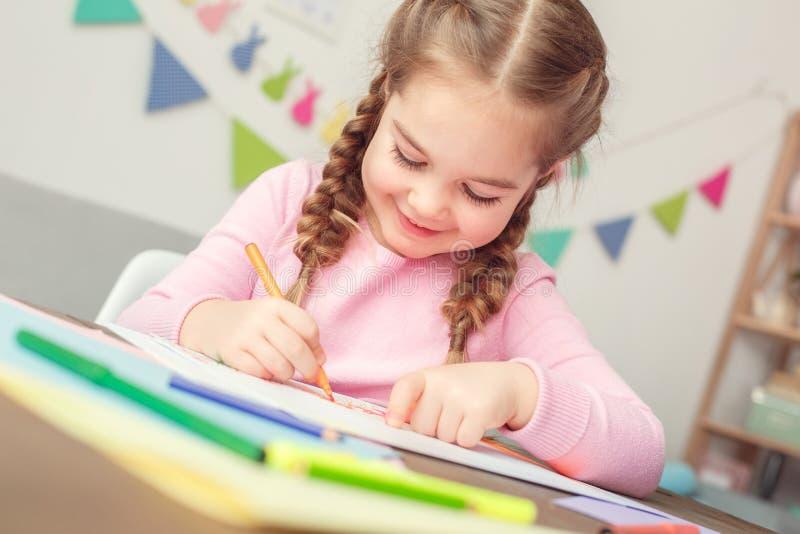 Małego ślicznego dziewczyny edukaci pojęcia siedzący rysunkowy kartka z pozdrowieniami dla kobiety ` s dnia radosnego w domu zdjęcia stock