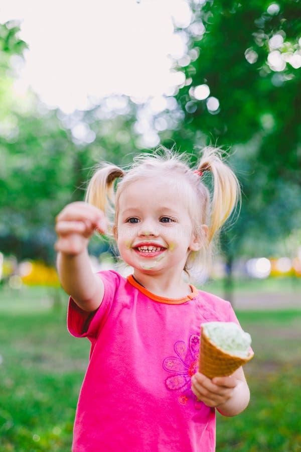 Małego śmiesznego dziewczyny blondynki łasowania słodki błękitny lody w gofr filiżance na zielonym lata tle w parku mażący jej tw zdjęcie royalty free
