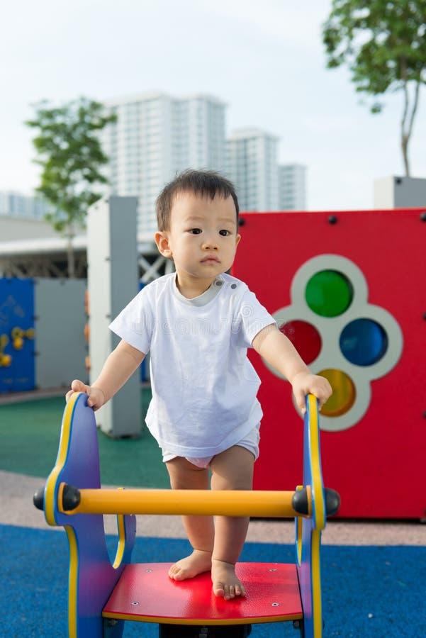 Małego berbecia Azjatycka chłopiec ma zabawę na boisku fotografia stock