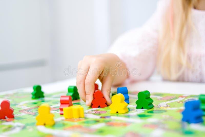 małego blondynki dziewczyny chwyta postaci w ręce czerwoni ludzie kolor żółty, błękit, zieleni drewniani układy scaleni w dziecko zdjęcie stock