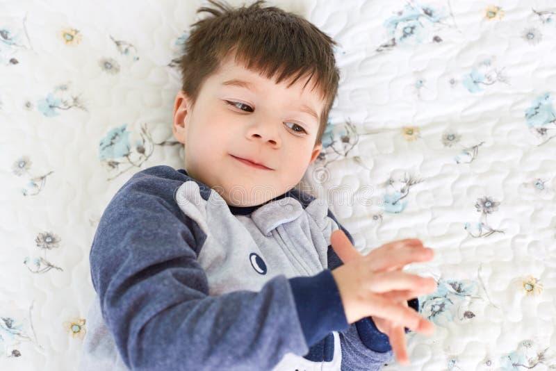 Małego brunet urocza chłopiec z interesującym pojawieniem, jest ubranym pyjamas, kłama na wygodnym białym łóżku na miękkich bedlo zdjęcia royalty free