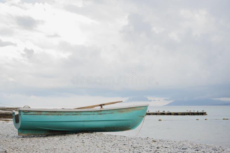 Małego drewnianego połowu lazurowa łódź na otoczaka wybrzeża czerni morza plaży fotografia stock