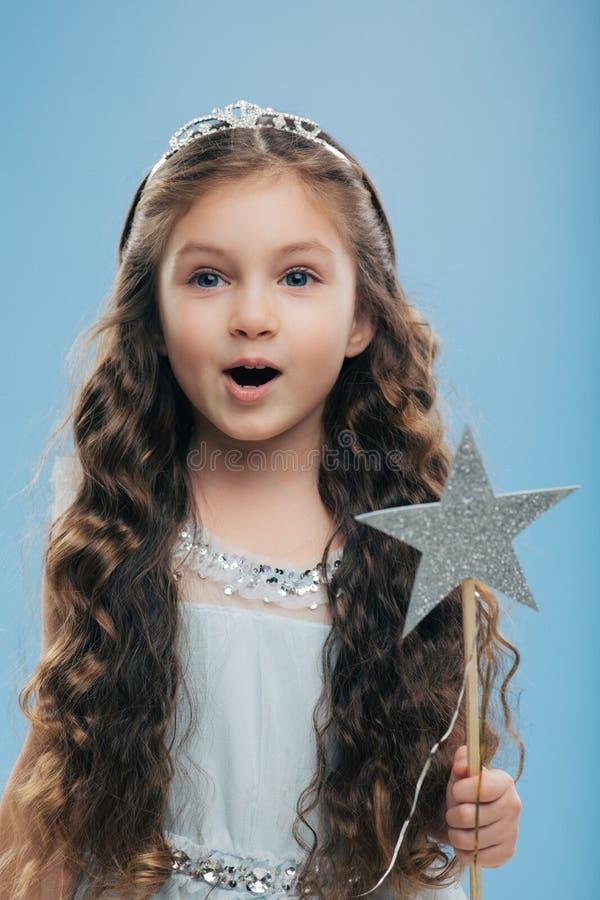 Małego małego dziecka żeński princess jest ubranym koronę i suknia, trzyma magiczną różdżkę, długie ciemne kędzierzawego włosy po zdjęcia stock