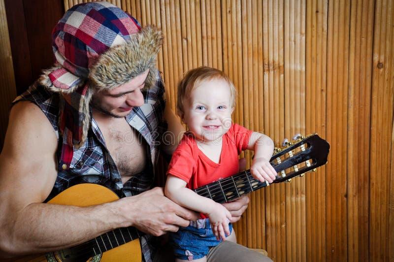 Małego dziecka dziecko z jego modnisia ojcem bawić się gitarę na drewnianym tle fotografia royalty free