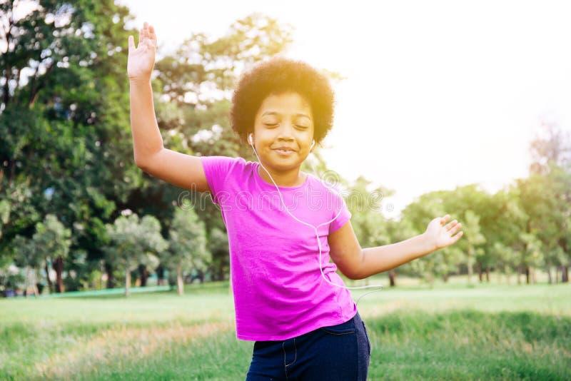 Małego dziecka słuchanie muzyka w zieleń parku i taniec zdjęcie royalty free