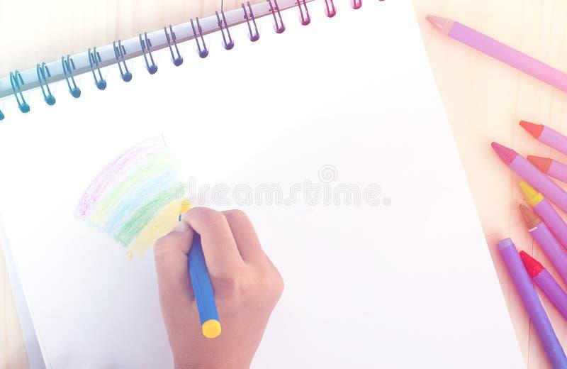 Małego dziecka ` s ręki rysunek coś z żółtą kredką na bielu obraz stock