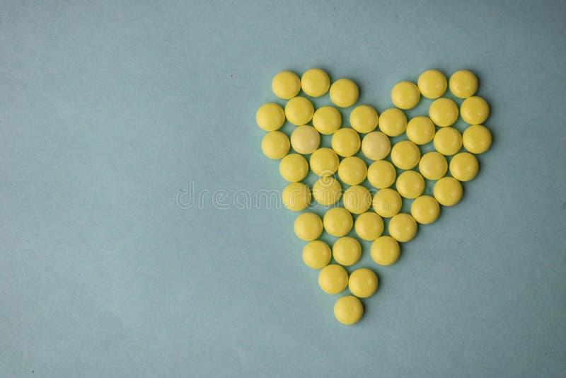 Małego medycznego pharmaceptic round żółte pigułki, witaminy, leki, antybiotyki w postaci serca na błękitnym tle, tekstura fotografia royalty free