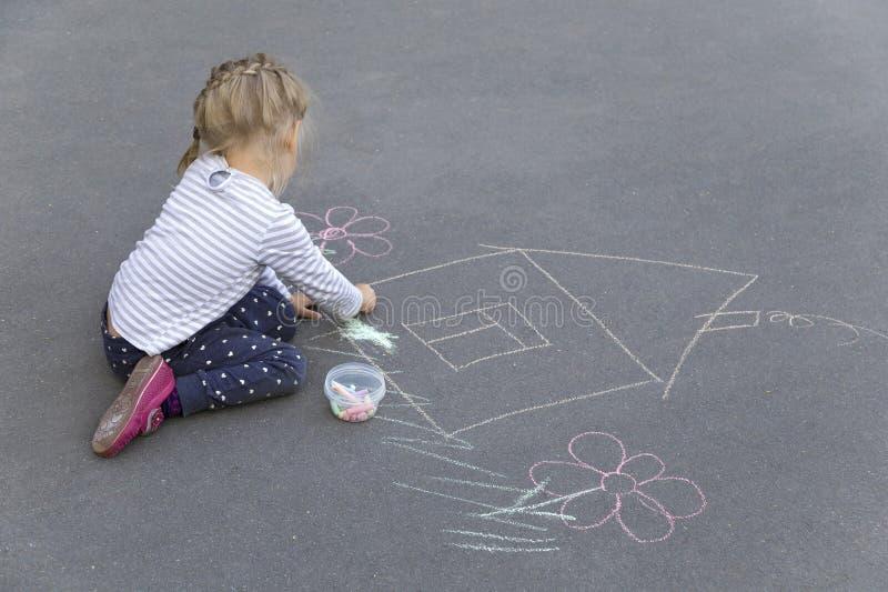 Małego preschool caucasian dziewczyna rysuje dom z pisze kredą zdjęcia stock